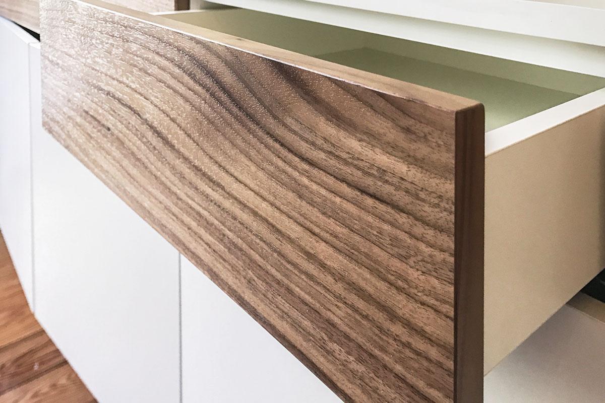 Das dunkle Holz bildet einen geschmackvollen Kontrast zur weißen Regalwand