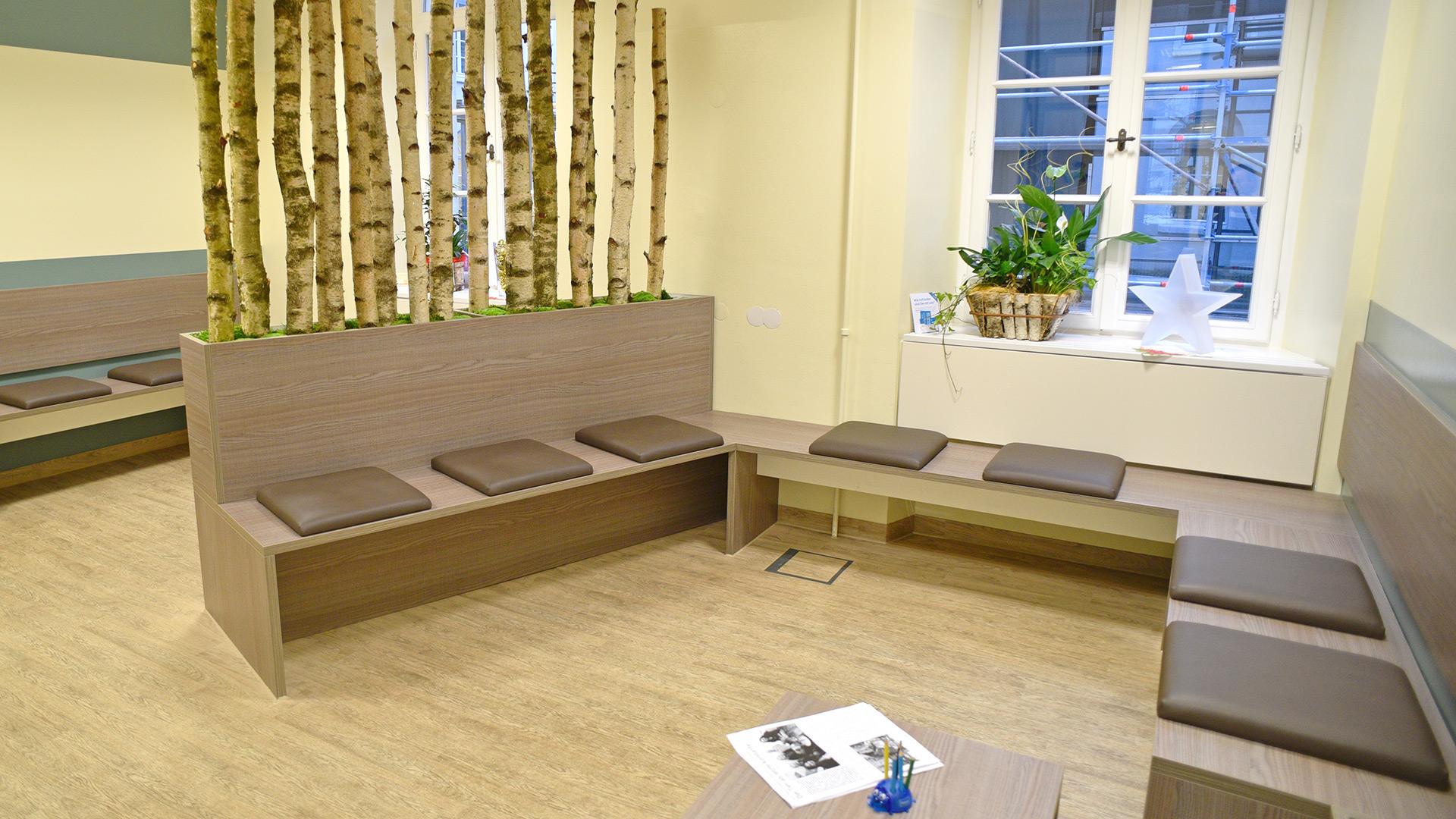 Angenehmer Wartebereich mit Raumteiler aus Birkenstämmen