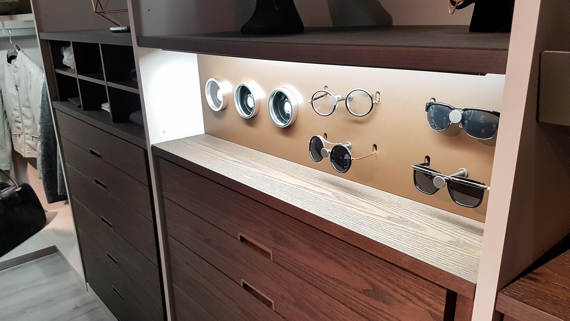 Brillenhalter und Uhrenwender. Dieses Ankleidesystem nimmt Accessoires gekonnt auf und inszeniert sie durch Beleuchtung