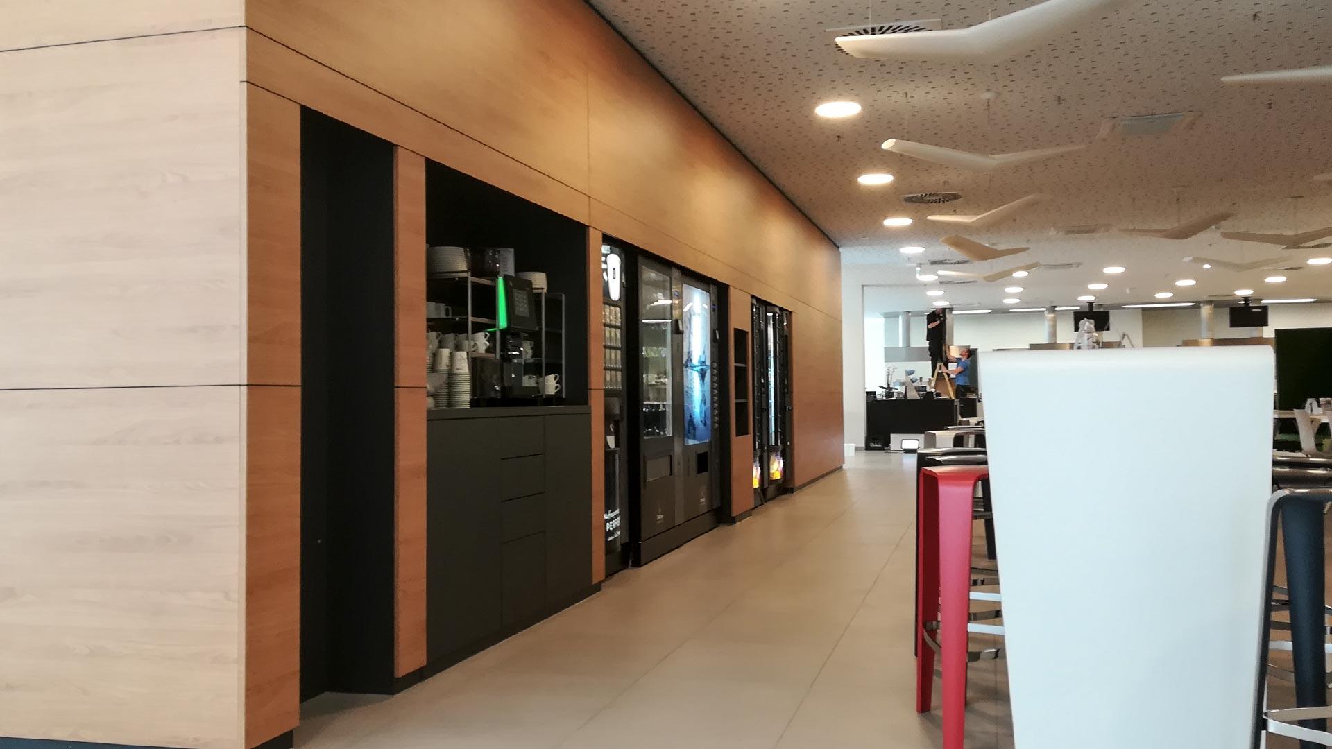 Der Raumteiler fasst Snack- und Getränkeautomaten, Kaffeebar, Tassenrückgabe und Mikrowelle.