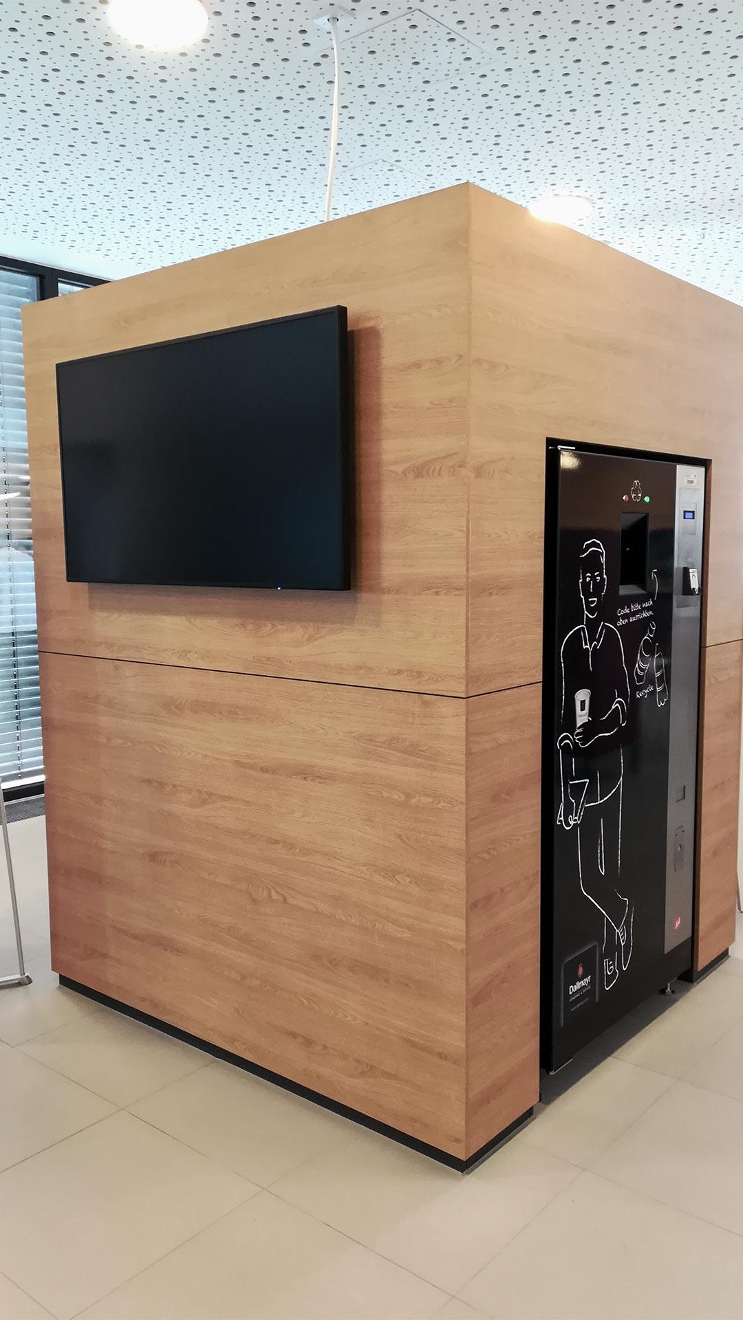 Der Einbauschrank im Eingangsbereich der Haribo Firmenzentrale beinhaltet einen Kaffeeautomaten und einen Bildschirm zum Anzeigen der Speisekarte.