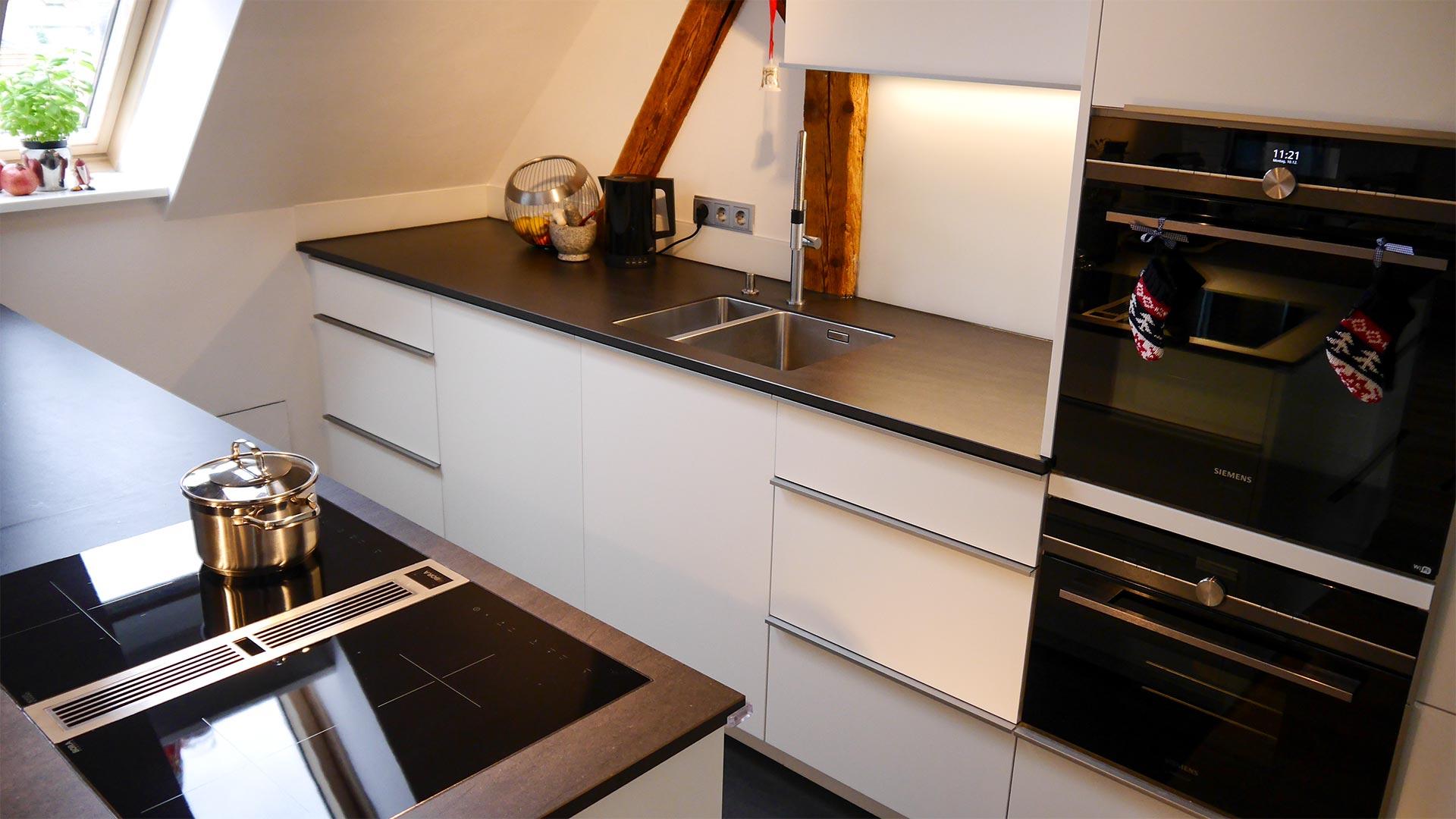 Die Küchenzeilen sind so angeordnet, dass das Licht ungehindert durchs Dachfenster einfallen kann.
