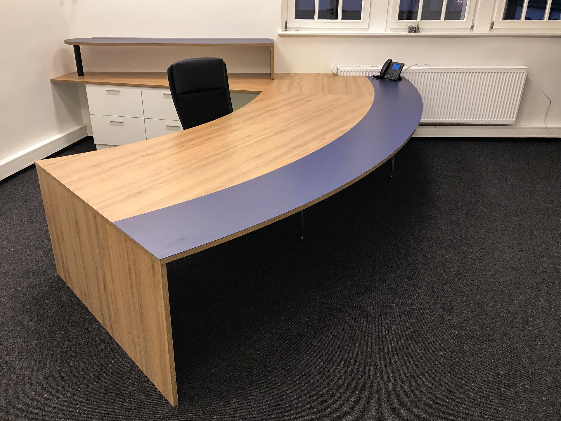 Der große, geschwungene Schreibtisch mit blauer Naturkautschukauflage ist ideal geeignet um mehrere Klienten zu empfangen und fokussiert das Gespräch automatisch auf den Notar.