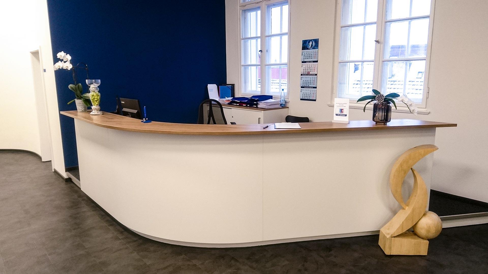 Die Empfangstheke in matt weiß mit Holzarbeitsplatte, Tretford Teppichboden in anthrazit und der blauen Wand definiert die Gestaltungsprinzipien für die gesamte Innenarchitektur.