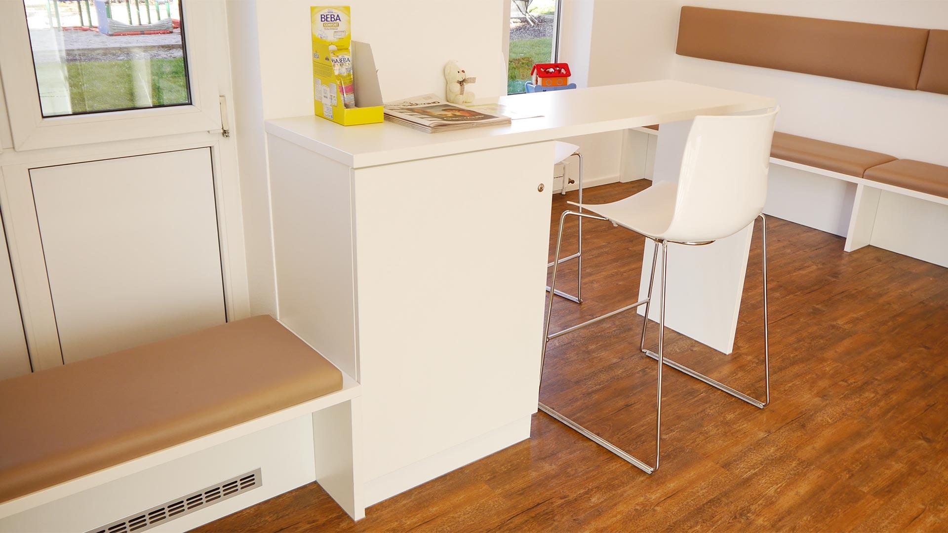 Einige Sitzbänke dienen als Heizkörperverkleidung. Der Stehtisch verfügt über Stauraum in Form eines Unterschranks.