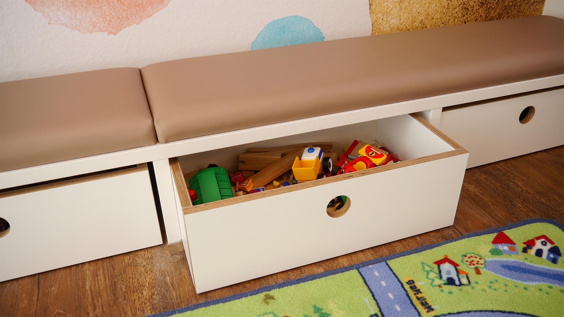Unter den Kindersitzbänken im Wartezimmer befinden sich Spielzeugboxen.