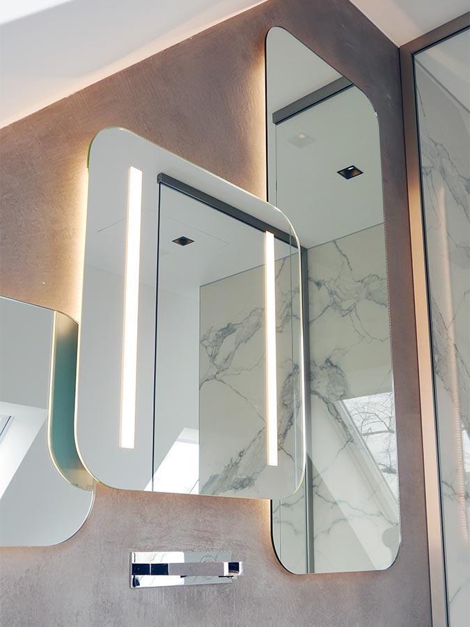 Runde Ecken und indirekte Beleuchtung charakterisieren den Design-Spiegel