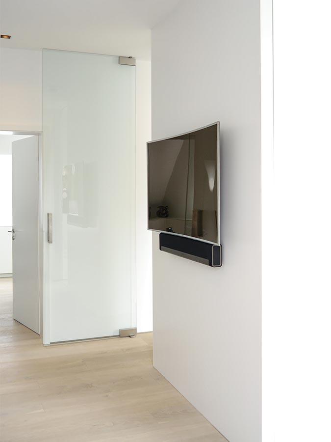 Auf der Rückseite des Trennwandmöbels ist ein TV-Gerät mit Soundbar aufgehängt