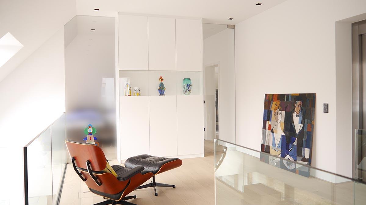 Das Trennwandmöbel mit Glastür und Festverglasung grenzt das Schlafzimmer vom Treppenaufgang ab.
