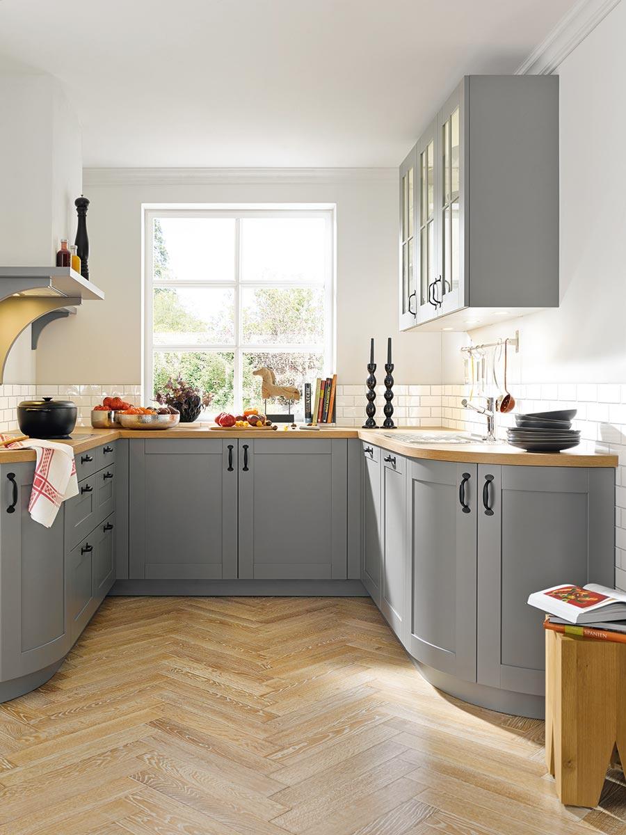 Landhausküche mit abgerundeten Unterschränken und passender Arbeitsplatte in zeitlosem Grau.