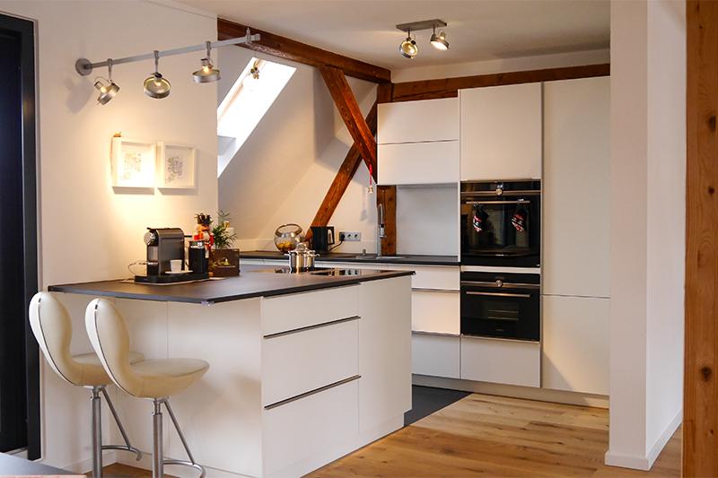 Fertige Einbauküche im Dachgeschoss. Ein Flächenabzug sorgt für ein offenes Interior Design.