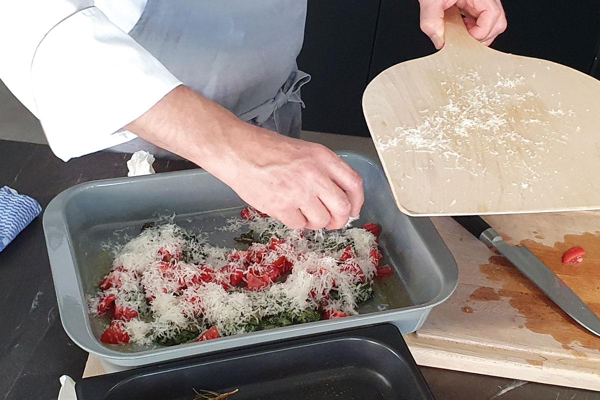 Verfeinerung der Spinatnocken mit Tomaten und Parmesan.