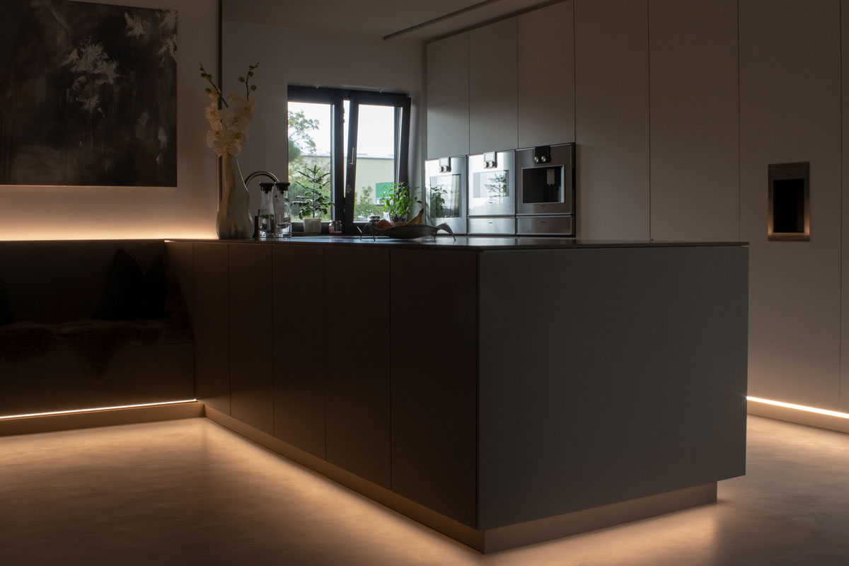 In dieser Schreinerküche schafft die indirekte Beleuchtung eine besondere Atmosphäre.