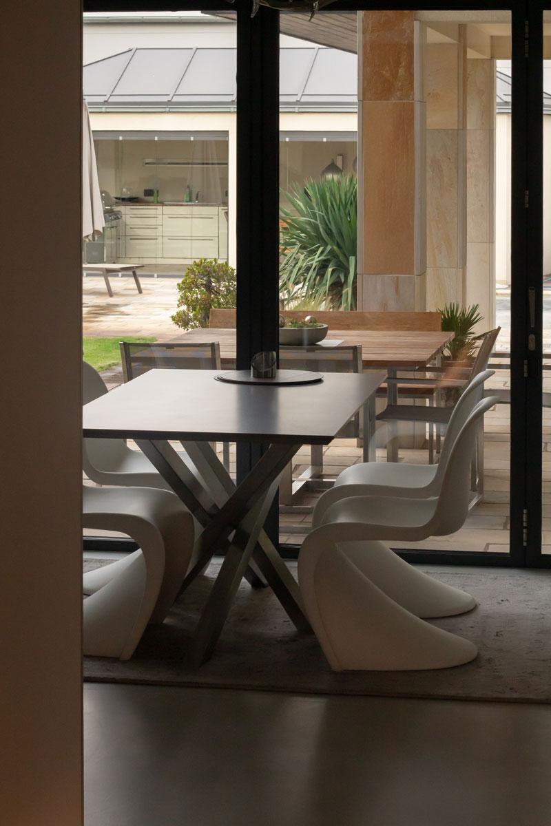 Der Esstisch mit Panton Chairs greift die Porzellankeramik-Arbeitsplatte wieder auf
