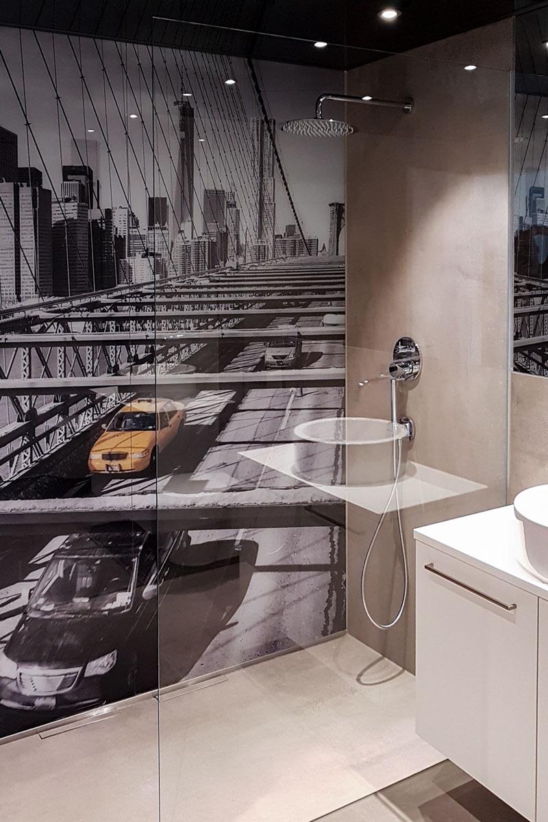 Die geräumige Duschkabine wird durch eine gläserne Wand angetrennt