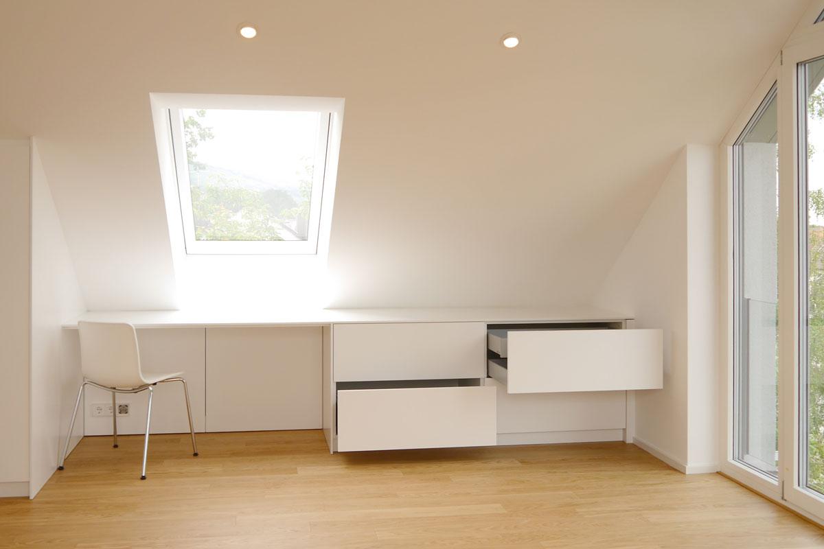 Der Schreibtisch ist perfekt in die Dachschräge und das Ankleidensystem integriert.
