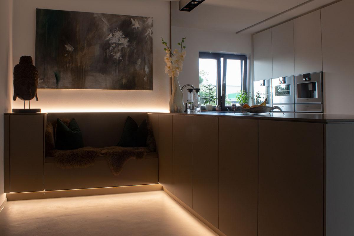 Die Sitzbank-Nische wird durch indirekte Beleuchtung in das restliche Küchenkonzept integriert
