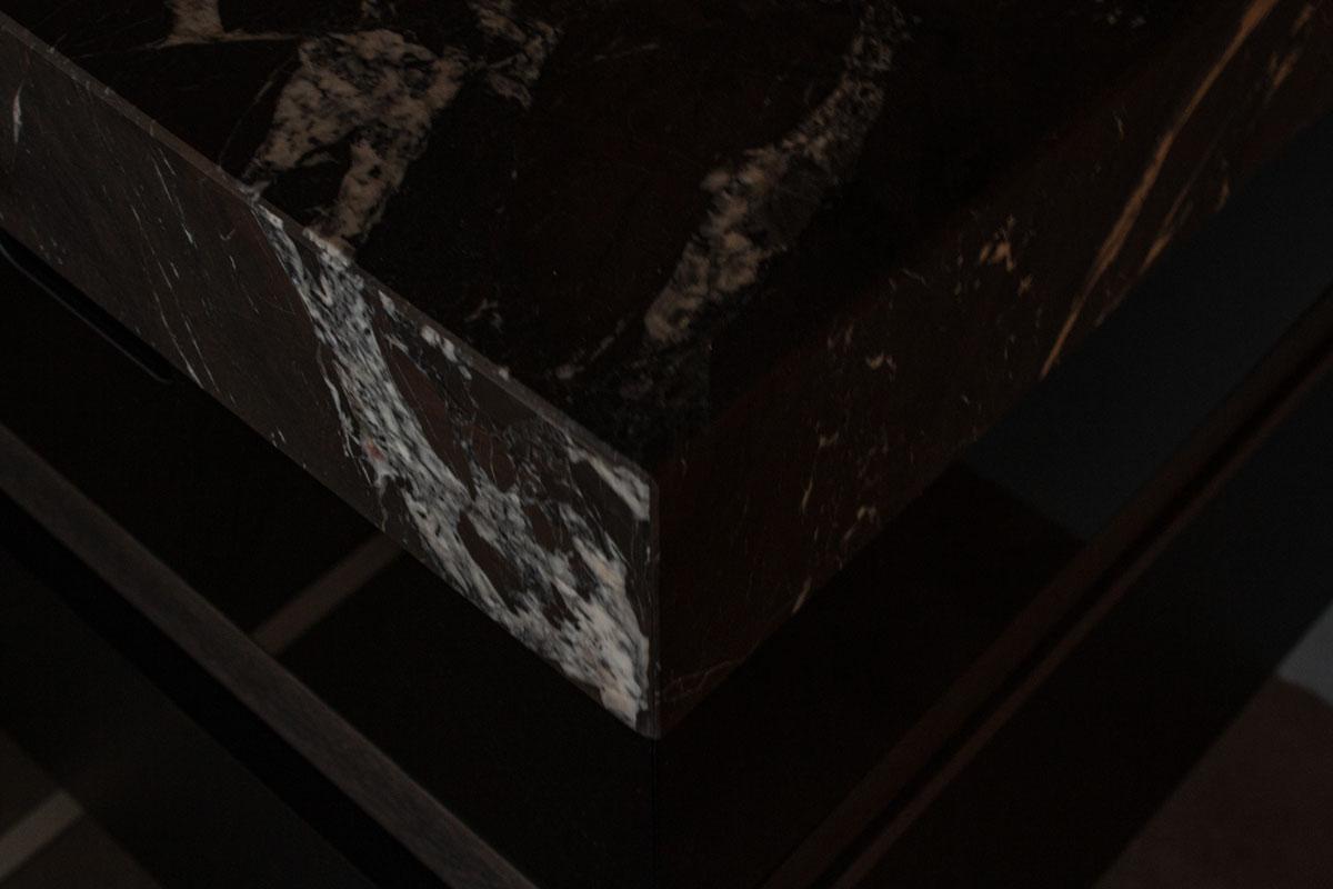 Die Maserung des Natursteins setzt spannende Akzente in der dunkel gestalteten Küche