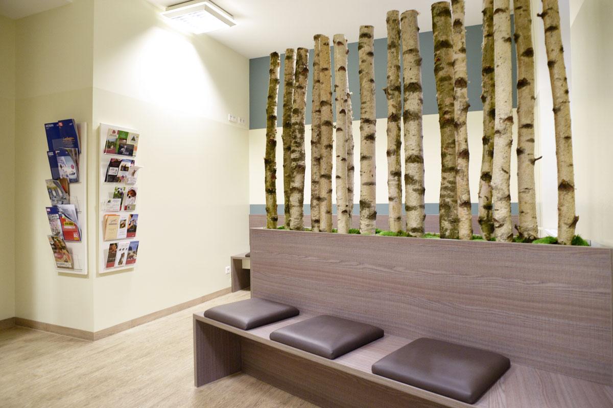 Wartebereich mit Trennwand aus Birkenstämmen