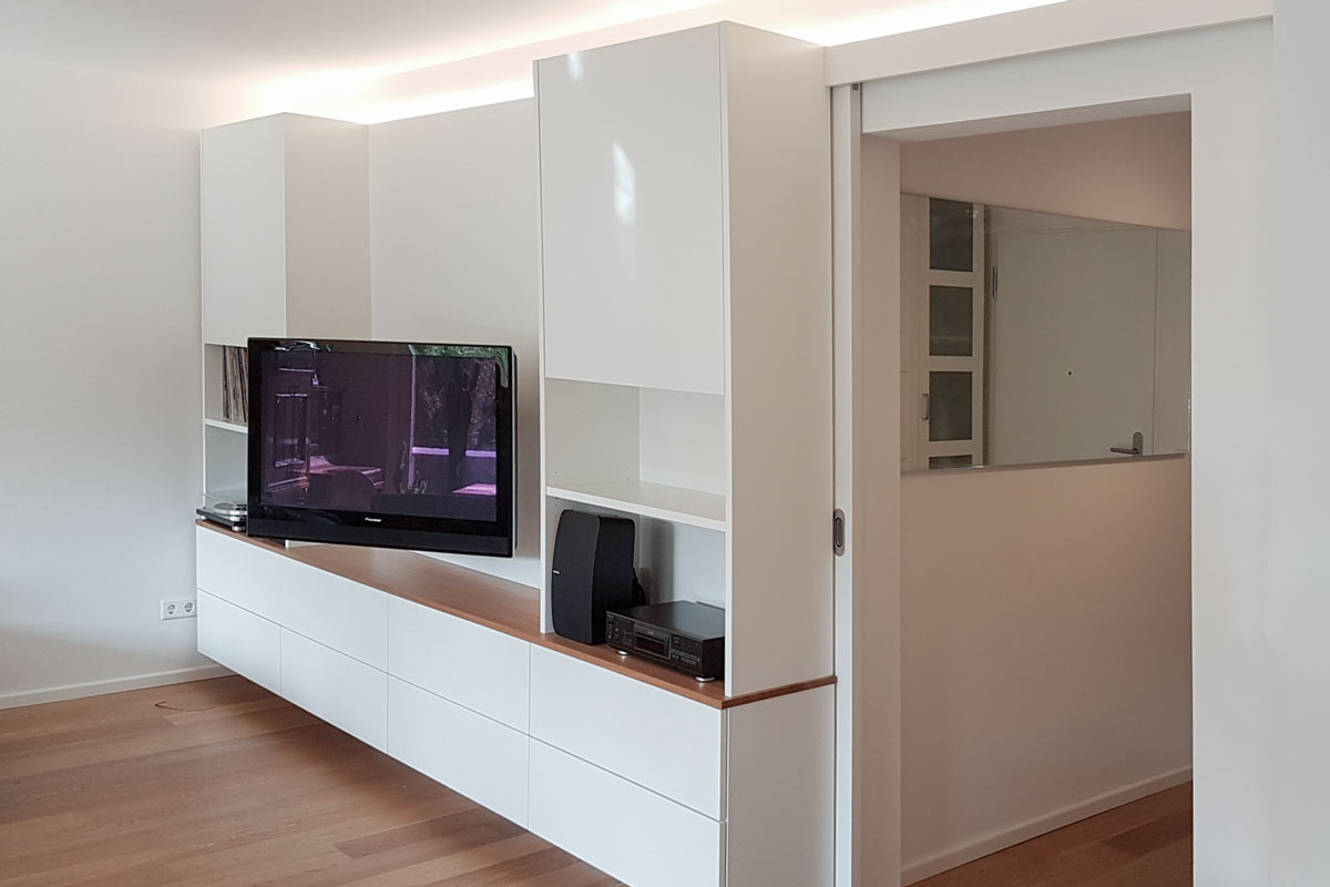 Mediamöbel mit TV-Arm, integrierter Schiebetür und indirekter Beleuchtung.