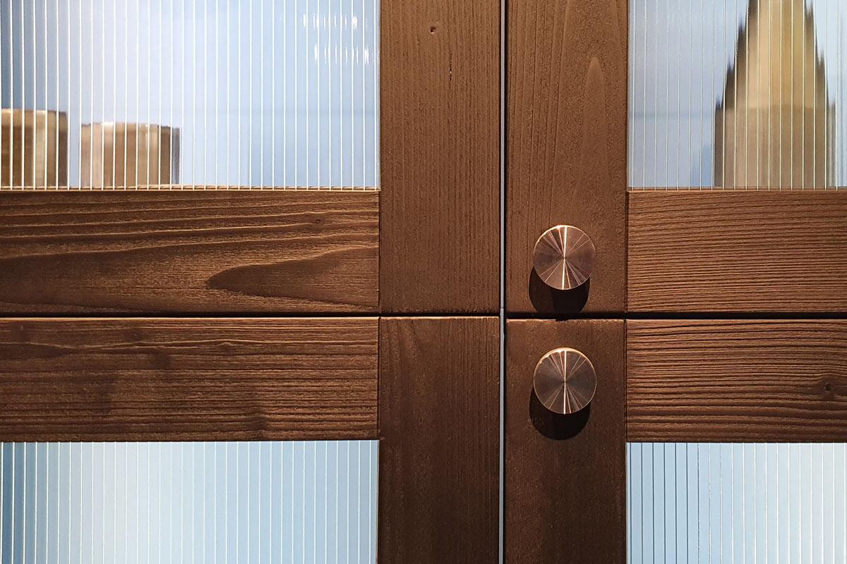 Beleuchtete Vitrine mit Strukturglas und breiten Holzrahmen